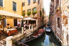 典型的微小的咖啡馆的许多访客在运河附近的威尼斯有长平底船和小船的 免版税库存图片