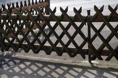 典型的德国在柏油碎石地面的格子工作篱芭熔铸的阴影 图库摄影