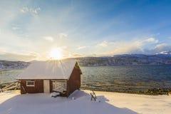 典型的挪威温暖和舒适房子位于湖边在 免版税库存图片