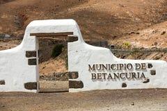 典型的自治市标志(白色曲拱门)在贝坦库里亚村庄附近 免版税库存图片