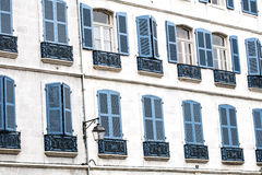 典型的门面的对准线与蓝色木窗帘的在欧洲 库存图片