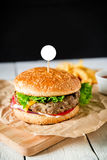 经典大汉堡包用牛肉、调味汁和炸薯条在黑暗的背景 美国鲜美食物 空白框架 免版税库存照片