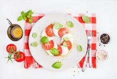 经典意大利人Caprese沙拉用蕃茄、无盐干酪di Buffala和新鲜的蓬蒿 免版税库存图片