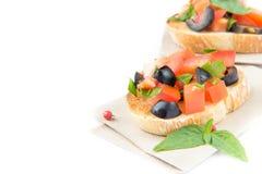 经典意大利开胃菜bruschetta用蕃茄、蓬蒿和blac 免版税图库摄影