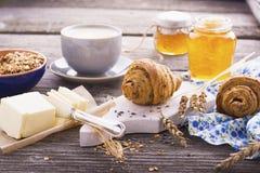 经典早餐用谷物、新月形面包和蜂蜜在土气样式的木背景服务 免版税图库摄影