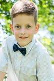 经典样式的逗人喜爱的矮小的时髦的男孩在公园 免版税库存照片