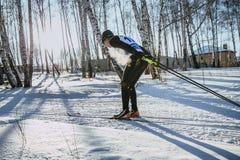 经典样式的年轻男性滑雪者在体育的冬天森林赛跑,蒸发,当呼吸 免版税库存照片