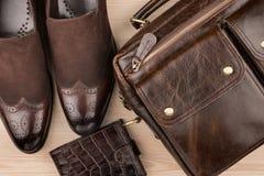 经典棕色鞋子、公文包和钱包在木地板上 库存照片