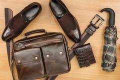 经典棕色绒面革鞋子、公文包、传送带和伞在木地板上 免版税库存图片