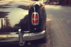 经典汽车背面图在都市的路停放了 免版税库存图片