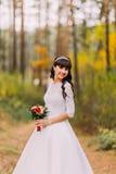 经典白色礼服的美丽的无辜的年轻深色的新娘在森林足迹站立 免版税图库摄影