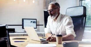 戴经典眼镜和工作在木桌上的成人专业商人在现代coworking的演播室 免版税图库摄影
