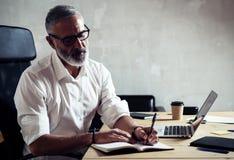 戴经典眼镜和工作在木桌上的成人成功的商人在现代顶楼演播室 博若莱红葡萄酒 免版税库存照片