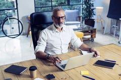 戴经典眼镜和工作在木桌上的成人成功的商人在现代coworking的演播室 时髦 免版税库存照片