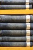 经典蓝色牛仔裤纹理的混合大小与纸标记展览的在木架子陈列室 免版税库存照片
