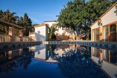 经典西班牙样式的二层楼的房子与一个大游泳池 图库摄影