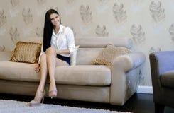 典雅和性感的妇女坐一个沙发在一间豪华屋子 免版税库存图片