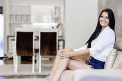 典雅和性感的妇女坐一个沙发在一间豪华屋子 库存照片