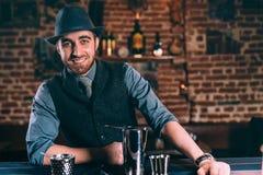 典雅和时髦的侍酒者佩带的帽子和葡萄酒衣裳画象,当准备饮料和鸡尾酒时 库存照片