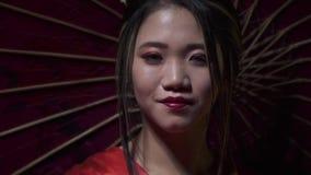 典雅的东方妇女展开与微笑的一个红色爱好者,并且用它,慢动作盖她的面孔 股票录像