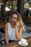 典雅的事务女性在一个室外咖啡馆讲话在手机 免版税图库摄影