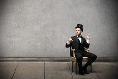 年轻典雅的人坐椅子 免版税库存照片