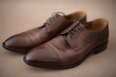 典雅的使用的棕色皮革男性鞋子在与小插图作用的坚实米黄背景设置了 图库摄影