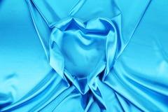 从典雅的发光的蓝色丝绸的心脏形状 免版税图库摄影