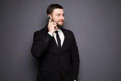 典雅的商人有在一个巧妙的电话的一次严肃的交谈反对黑暗的背景 库存图片
