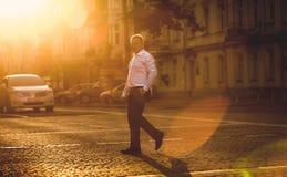 典雅的商人横穿街道被定调子的射击晴天 免版税图库摄影