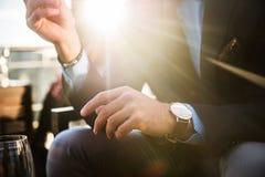 典雅的商人生活方式照片佩带豪华手表和吃晚餐在餐馆在成功的工作日以后 库存照片