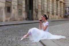 典雅的在街道上的芭蕾舞女演员饮用的咖啡 免版税库存照片