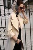 典雅的外套和丝绸围巾的美丽的妇女在头 图库摄影