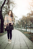 年轻典雅的女孩在秋天期间的公园 免版税图库摄影