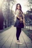 年轻典雅的女孩在秋天期间的公园 图库摄影