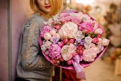 典雅的女孩微笑举行不同的桃红色和紫色花巨大的花束  库存照片