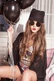 典雅的女孩模型在组合、玻璃和圆顶硬礼帽摆在 拿着捆绑og baloons的妇女 免版税库存图片