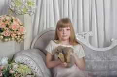 典雅的女孩用灰色兔子在手上 免版税图库摄影