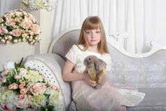 典雅的女孩用灰色兔子在手上 免版税库存图片