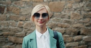 典雅的女孩画象看照相机微笑的时髦的太阳镜的室外 股票录像
