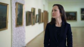 典雅的女孩看图片在现代美术博物馆  年轻女人观看的艺术作品在的绘画 股票录像