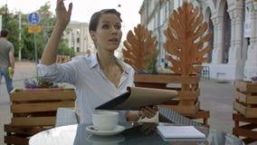 典雅的女实业家要求侍者,当坐在咖啡店,女性执行委员时工作午餐断裂  免版税图库摄影