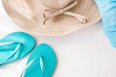 典雅的女性草帽、蓝色拖鞋和海滩套在具体白色背景,暑假,海边,干净的最低纲领派 免版税库存照片