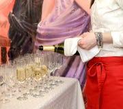 典雅的女服务员倒香槟入小组玻璃 图库摄影