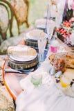 典雅的婚礼桌设置的部分在土气样式的 桌由葡萄酒杯,可爱的蜡烛装饰 免版税图库摄影