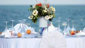 典雅的室外婚礼表有海视图 免版税库存照片