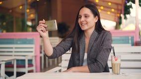 典雅的少妇打网上电话使用放松在露天咖啡馆的智能手机在桌上用奶昔和谈话 影视素材