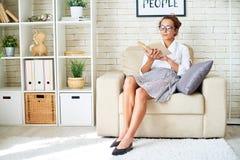 典雅的少妇阅读书在家 免版税库存图片