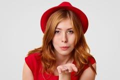 典雅的年轻女性做空气亲吻,表现出她的爱给丈夫,打扮用时兴的红色帽子和T恤杉,姿态室内ag 免版税库存图片
