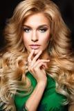 典雅的性感的白肤金发的妇女画象有长的卷发和魅力构成的 免版税图库摄影